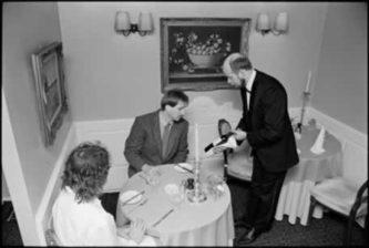 Philip Temple, Orsini's proprietor, presenting a bottle of wine to a customer, 1988