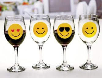 Novelty stemware glass set includes four cute glasses that each feature one popular yellow smiling emoji.